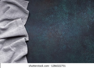 Gray tablecloth from left side of dark background top view with copy space