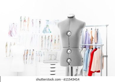 gray tailoring mannequin on a background of hanging clothes, sketches and a sewing machine