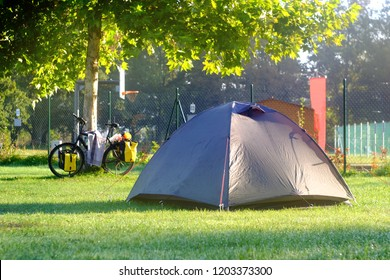 gray tent stands on the grass next to the bike for traveling with yellow bags, the theme of bicycle tourism and recreation