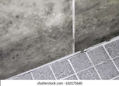 Gray tile grout in a home shower that has broken apart and needs repair. Cracked and split grout in a house shower corner between the wall and floor that needs fixing.