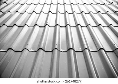 Gray tile roof floor background. Closeup roofing texture pattern. Materials to build a house for sun and rain protection. White backdrop with top rays light.