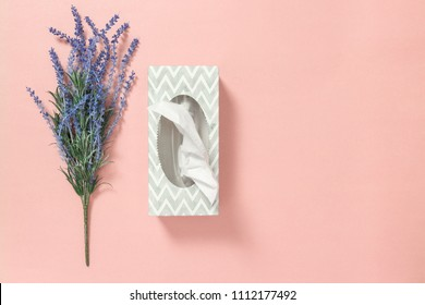 Gray tissue box and blue lavender on pastel pink background.
