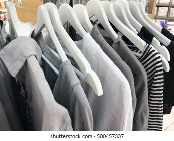gray tone linen clothes hanging on a rack in a designer clothes store
