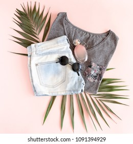Gray t-shirt, denim shorts, silver rings, perfume bottle, sunglasses, green leaves on a pale pink pastel background