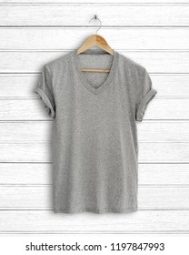 Gray t-shirt hang on vintage wood background.
