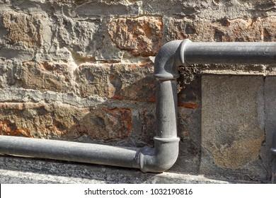 Gray tube on thebrick wall for gas trasportation