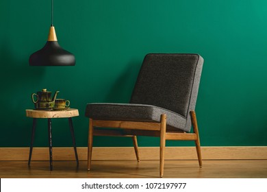 Gray upholstered chair by an empty teal green wall and an industrial ceiling lamp over a wooden side table in a minimalist living room interior