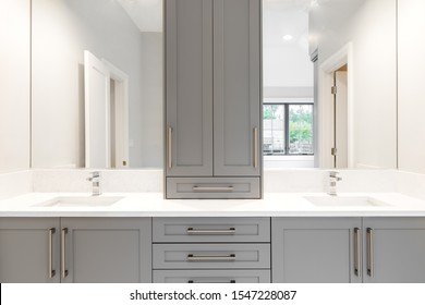 A gray vanity in a large luxurious bathroom with granite counter tops and chrome fixtures.