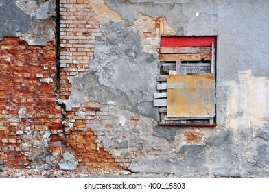 Gray wall of abandoned building with peeling plaster, red brick and the boarded-up window.