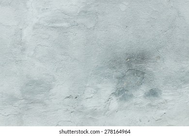 gray wall with cracks and scuffed and dark stain