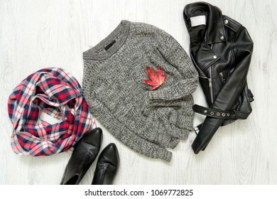 Gray warm sweater. Black jacket, checkered scarf and boots. Fashionable concept