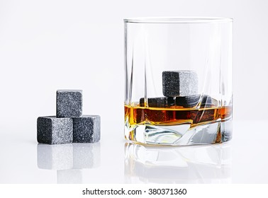 Gray whiskey stones in the glass. Close up view of whisky stones in the glass with whisky isolated on white background. Bourbon with ice Whisky Stones. Whiskey glass filled with cooling granite stones