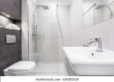 Gray and white bathroom with shower, basin and toilet