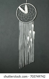 Gray white dream catcher on dark gray textured background. Texture of concrete, copy space for text