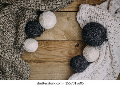Gray and white knitting wool. The background is aged wood. Knitting needles, scissors, knitted fabric.