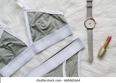 Gray white linen set for sports on a white fur. Watches and lipstick. Fashionable concept, top view