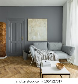 Gray and white living room with couch, coffee table and vintage tiled stove