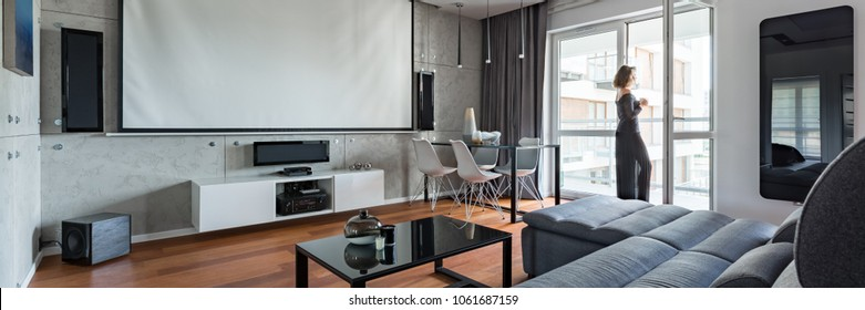 Gray and white living room with sofa, table, balcony and projector screen, panorama