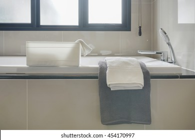 Gray and white towel and bathtub in modern interior bathroom