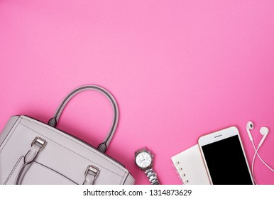 gray women bag and smartphone, notebook, watch on a pink background. view from above. copy space