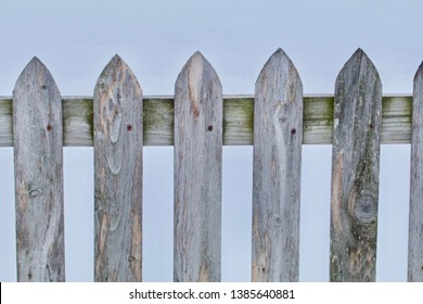A gray wood pickett fence closeup appears.