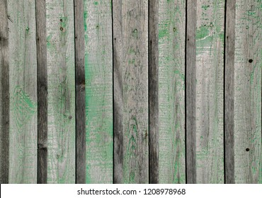 gray wooden fence with spots of green paint