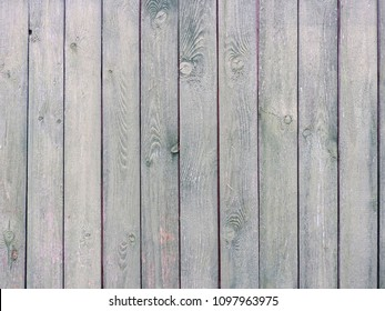 A gray wooden fence with tightly nailed vertical slats. Background structure.