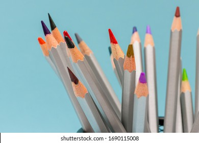gray wooden pencils with colored rods on a blue background