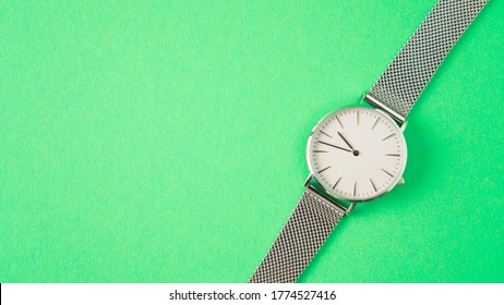 gray wristwatch on a green background. isolated woman watch. time is running away concept. watch advertisement