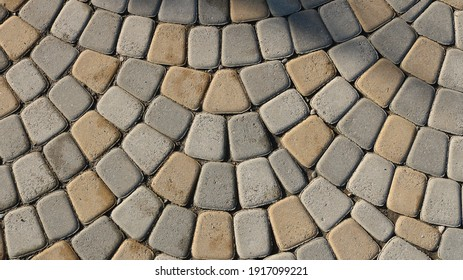 gray-beige natural processed stone in the structure of a paved pavement as a textured relief background, a top view of the surface of a city square with a semicircular laying of cubic blocks