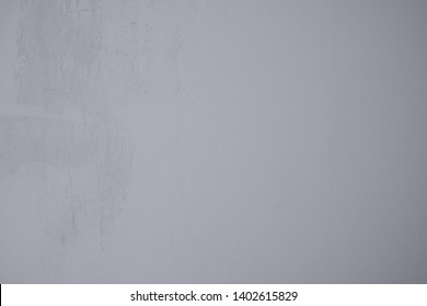 Gray-blue wall in industrial design as background and art design. Plastered concrete wall with rough structures and pastel colors.