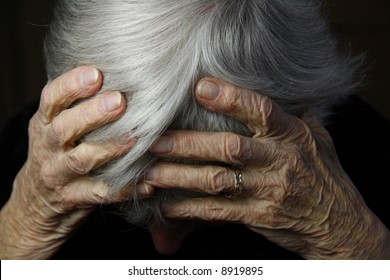 grayed haired lady holding head in severe pain