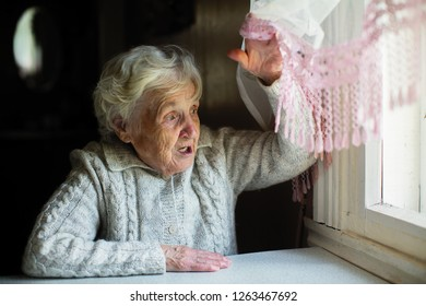 Gray-haired elderly woman looks out the window.