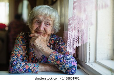 Gray-haired elderly woman portrait, sits and looks out the window.
