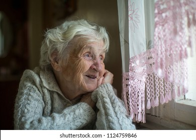 A gray-haired elderly woman sits and looks out the window.