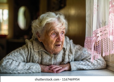 Gray-haired elderly woman sits and looks out the window.