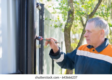 A gray-haired male construction worker painting black metal fence pipe with a brush