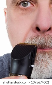 Gray-haired man shaves his beard with an electric razor