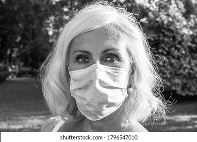 Gray-haired middle-aged woman wearing protective surgical mask. Portrait of a middle-aged medical woman with bright eyes in a surgical mask staying outdoors in park, monochrome shot