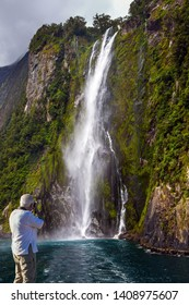 The gray-haired tourist photographs the landscape. Magnificent waterfall crashes down from the cliff. Tourist cruise aboard the Milford Sound fjord. New Zealand. Concept of exotic tourism