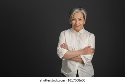 Graying pretty woman in white shirt stands arms-crossed isolated on dark gray background. High quality photo.