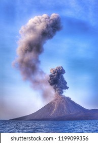 Grayish white smoke billows out from the crater of the Anak Krakatau mountain