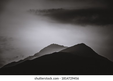 A grayscale beautiful shot of mountain scenery and skyscape in a foggy weather