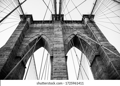 A grayscale low angle shot of a Brooklyn Bridge in New York City