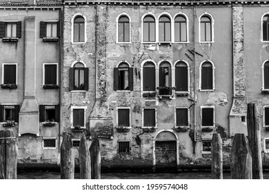 A grayscale shot of the ancient buildings with weathered exterior walls in Venice, Italy