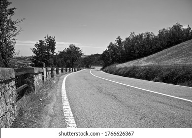 A grayscale shot of an asphalt road at the side of a hill with trees and a clear sky in the background
