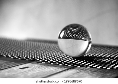 A grayscale shot of a glass lens ball on a black metal grid