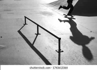 A grayscale shot of a male doing tricks with a skateboard