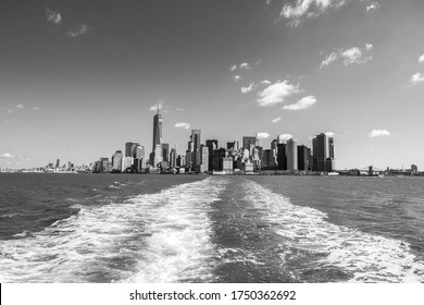 A grayscale shot of New York's skyscrapers on a water surface foreground