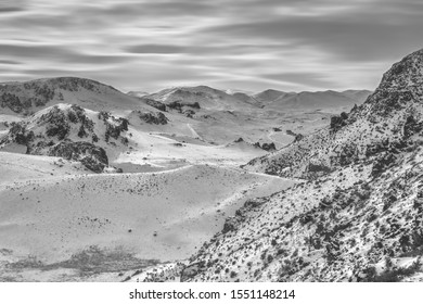 A grayscale shot of snowy mountains covered in trees wit ha cloudy sky in the background